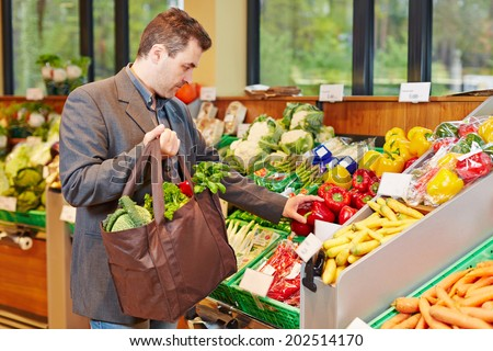 Businessman with shopping bag buying fresh vegetables in a supermarket