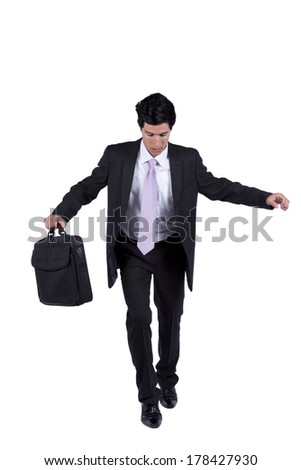 Businessman with slow walking with fear from falling (isolated on white) - stock photo