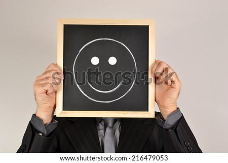 Businessman with smiling face in blackboard