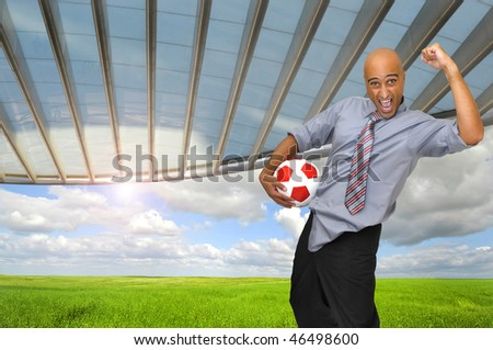 Businessman with soccer ball in a stadium like background - stock photo