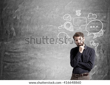 Businessman with speech and thought bubbles on blank chalkboard - stock photo