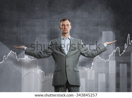 Businessman with spread arms and growing graphs on chalkboard