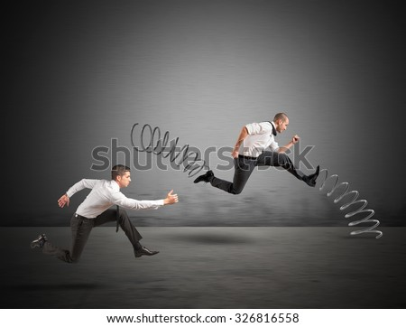 Businessman with spring runs against another businessman - stock photo