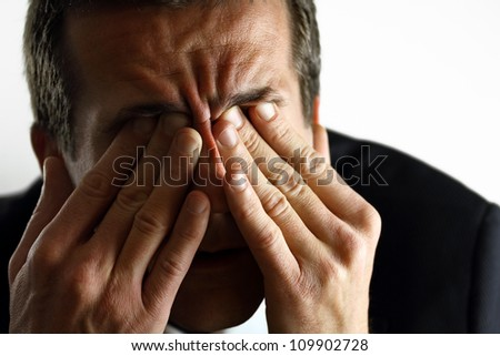 Businessman with stress rubbing his eyes - stock photo