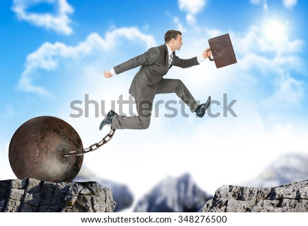 Businessman with suitcase and iron ballast  hopping over bottomless pit