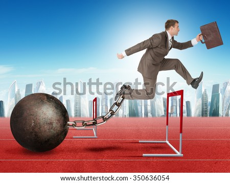 Businessman with suitcase and iron ballast jumping over treadmill barrier - stock photo