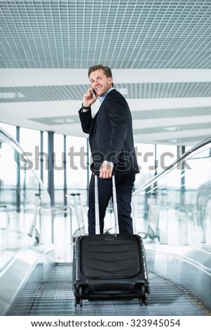 Businessman with suitcase at the airport - stock photo