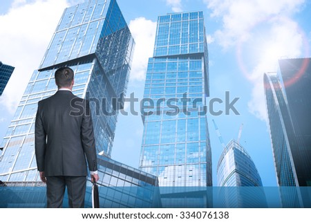 Businessman with suitcase on cityscape background, rear view