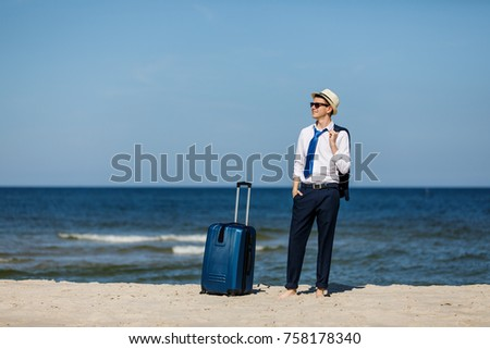 Businessman with suitcase relaxing on beach