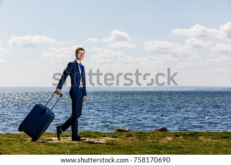 Businessman with suitcase standing at seaside