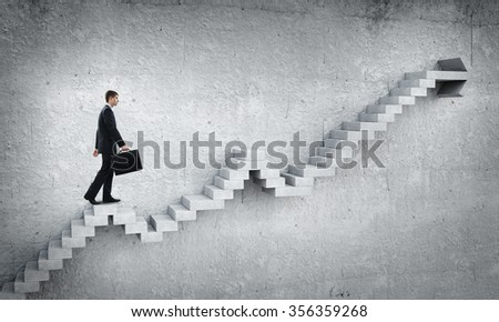 Businessman with suitcase stepping up stone staircase