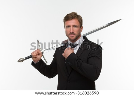 Businessman with sword isolated on white background. Handsome man in black business suit ready to have a battle. - stock photo
