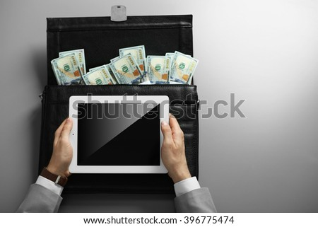 Businessman with tablet and brief case full of money money - stock photo