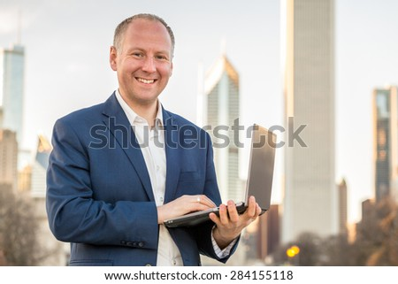 Businessman with tablet in front of office buildings - stock photo