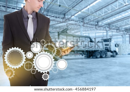 Businessman with tablet on hand , concept supply chain management logistics import export product at large warehouse.