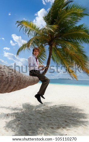 Businessman with tablet pc sitting on palm tree on the Maldivian beach and looking at camera smiling - stock photo
