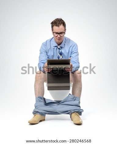 Businessman with tablet pc sitting on the toilet. Always online concept - stock photo