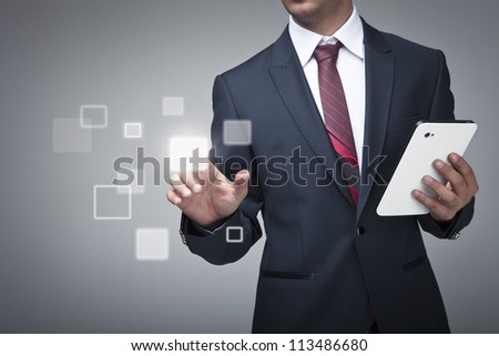 Businessman with tablet pushing on a touch screen interface - stock photo