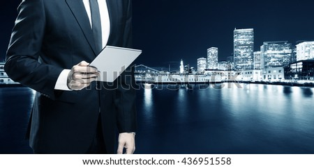 businessman with tablet with night scene of modern office buildings near water in san francisco - stock photo