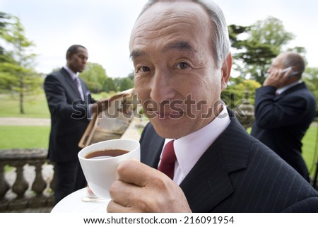 Businessman with teacup by colleagues on balcony, portrait - stock photo