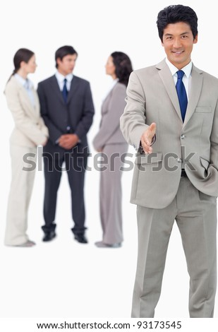 Businessman with team behind him offering hand against a white background