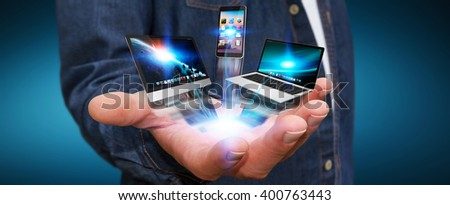 Businessman with tech devices computer phone and tablet in his hand