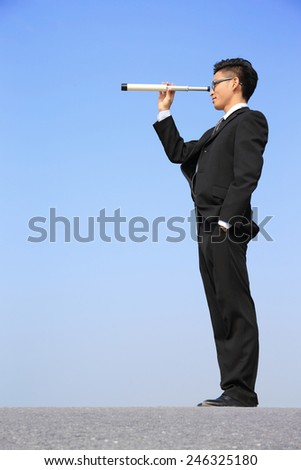 Businessman with telescope ( spyglass ) looking forward Prospects for future business with blue sky background, asian - stock photo