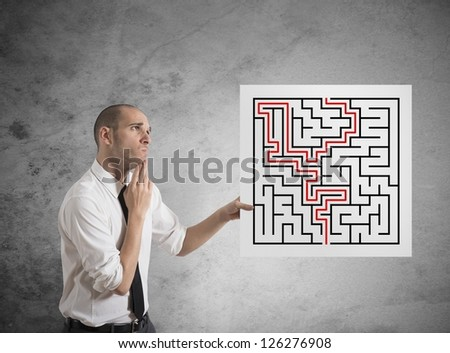 Businessman with the solution of a maze - stock photo