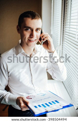 businessman with the tablet stands near a window and talking on the phone - stock photo
