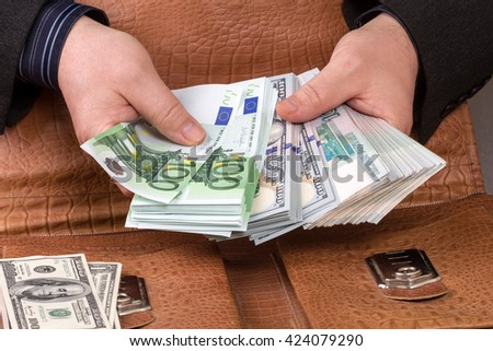 Businessman with three types of currency  (dollars, euros, rubles) and portfolio - stock photo