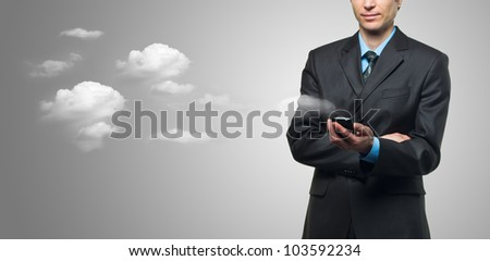 Businessman with touch screen phone and the clouds on grey background - stock photo