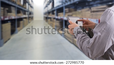 Businessman with touchscreen tablet checking inventory in stock room. Store house inspection - stock photo