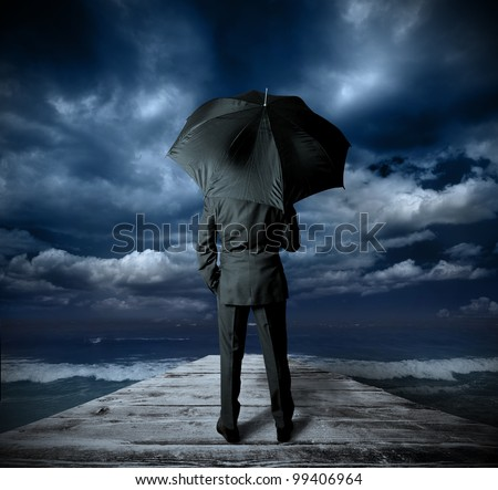 Businessman with umbrella against the storm - stock photo