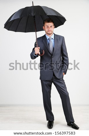 Businessman with umbrella. on gray background