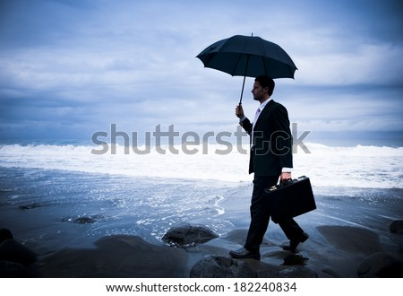 Businessman With Umbrella On Stormy Beach