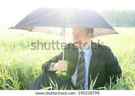 Businessman with umbrella outside on fresh  grass field - protection concept  business man sitting under an shadow on a green meadow on summer forest background  - stock photo