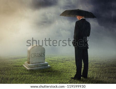 Businessman with umbrella standing near tomb of crisis - stock photo