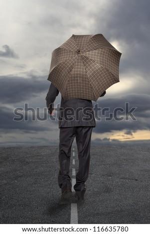 Businessman with umbrella under a stormy sky - stock photo
