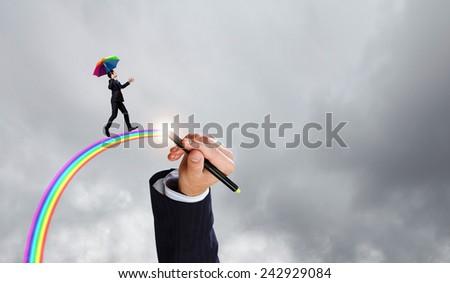 Businessman with umbrella walking on rainbow high in sky - stock photo