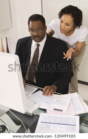 Businessman with woman gesturing while looking at computer at desk in office