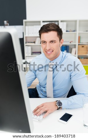 Businessman working at a desktop computer sitting reading information on a large monitor with a smile - stock photo