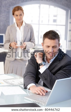 Businessman working at desk in bright office, getting coffee from pretty assistant, both smiling.?