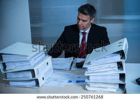 Businessman Working At Desk With Stack Of Folders - stock photo