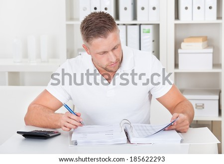 Businessman working at his desk in the office sitting writing notes in a short-sleeved white shirt