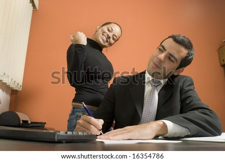 Businessman working at his desk while his secretary stands behind him pretending to be angry. Horizontally framed photo. - stock photo