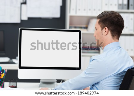 Businessman working at his desk with the blank screen of his desktop computer visible to the viewer - stock photo