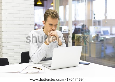 Businessman working at his laptop on the office in start-up - stock photo