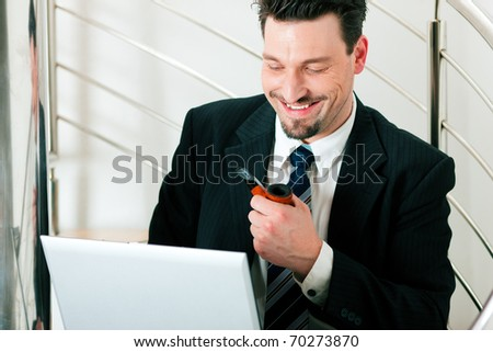 Businessman working at home with his laptop sitting on the stairs in his apartment - stock photo