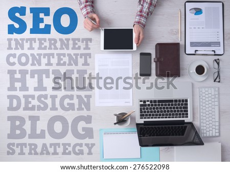 Businessman working at office desk and using a digital touch screen tablet, seo and web text concepts on left side, top view - stock photo