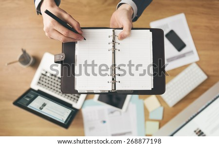 Businessman working at office desk and writing down notes on his agenda, laptop and financial report on background, top view. - stock photo